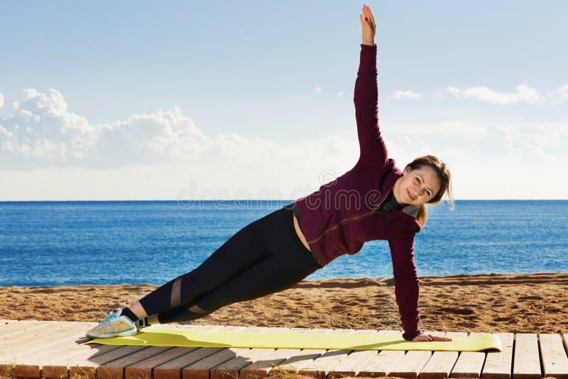 Νέα γυναίκα που κάνει το youga στην παραλία στοκ εικόνα με δικαίωμα ελεύθερης χρήσης