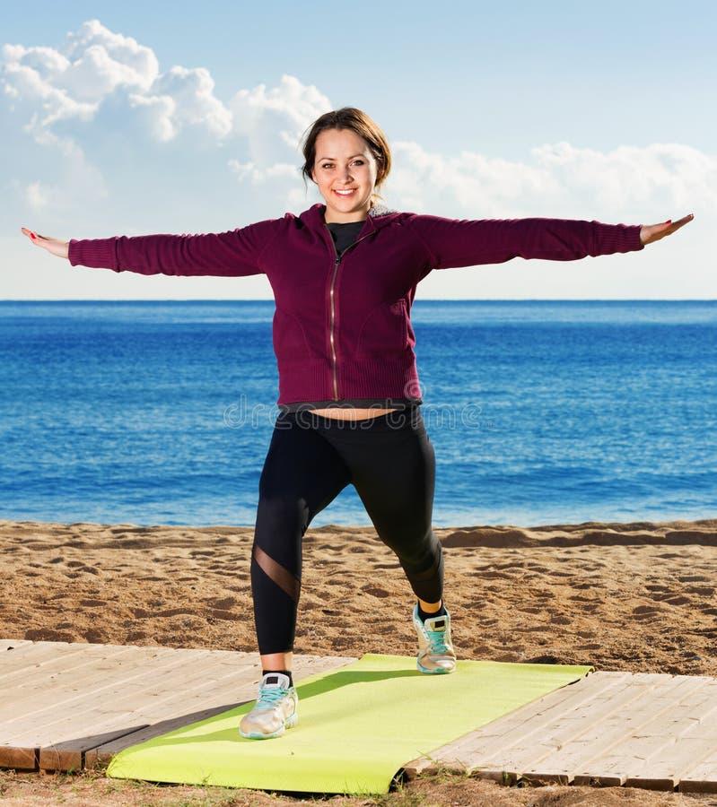 Νέα γυναίκα που κάνει το youga στην παραλία στοκ φωτογραφία με δικαίωμα ελεύθερης χρήσης