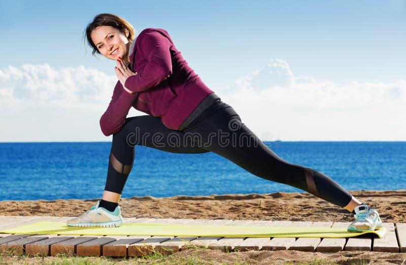 Νέα γυναίκα που κάνει το youga στην παραλία στοκ φωτογραφίες με δικαίωμα ελεύθερης χρήσης