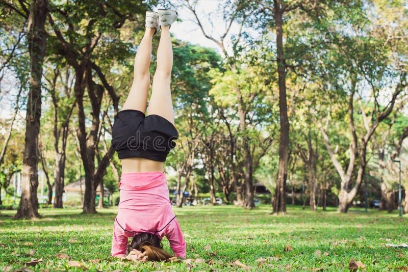Νέα γυναίκα που κάνει handstand την άσκηση γιόγκας για να χτίσει το σώμα ομορφιάς της στο πάρκο στοκ εικόνα με δικαίωμα ελεύθερης χρήσης
