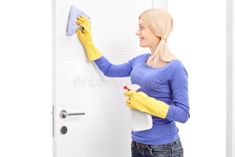 Νέα γυναίκα που καθαρίζει μια πόρτα με το ύφασμα στοκ φωτογραφίες