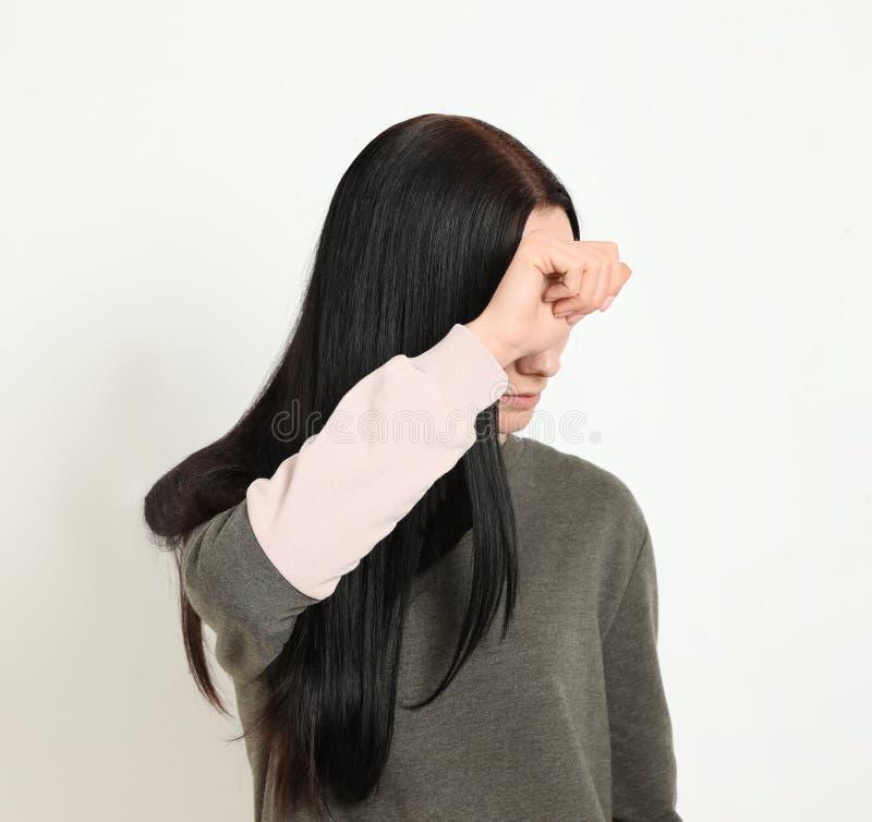 Νέα γυναίκα που καλύπτει το πρόσωπο στο άσπρο κλίμα στοκ φωτογραφίες