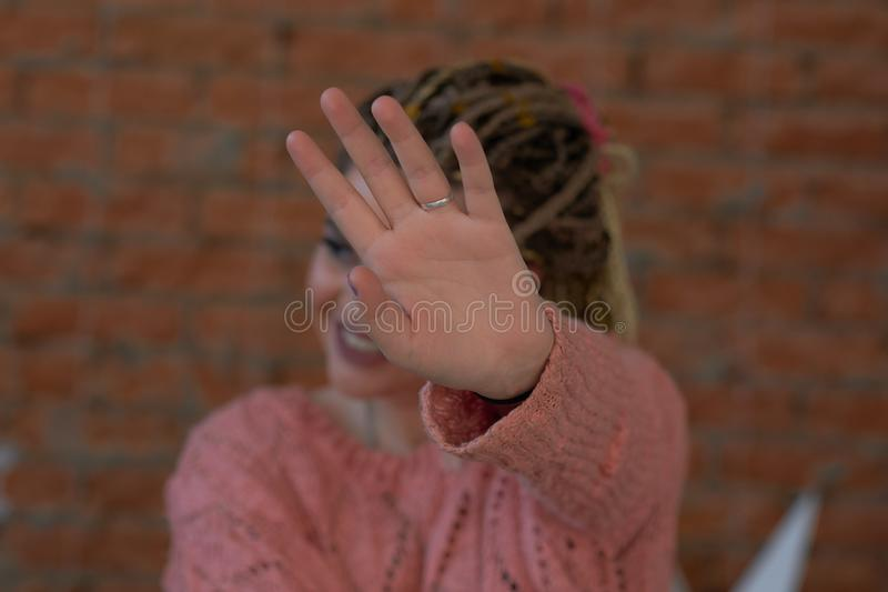 Νέα γυναίκα που καλύπτει το πρόσωπό της με το φοίνικα που λέει το αριθ. Κορίτσι που αρνείται την πρόταση, που κάνει τη χειρονομία στοκ φωτογραφία
