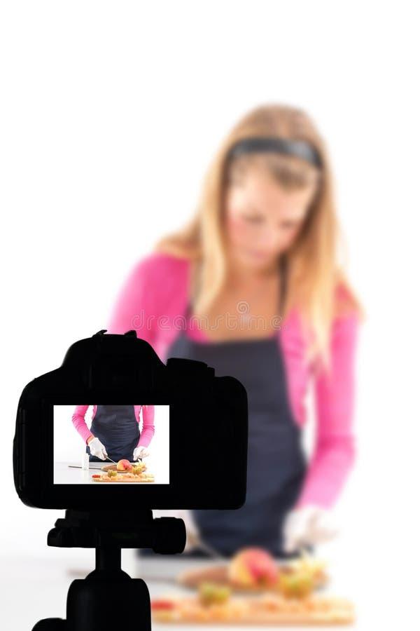 Νέα γυναίκα που καταγράφει την τηλεοπτική blog υγιή προετοιμασία τροφίμων της, έννοια Blog τροφίμων στοκ φωτογραφία με δικαίωμα ελεύθερης χρήσης