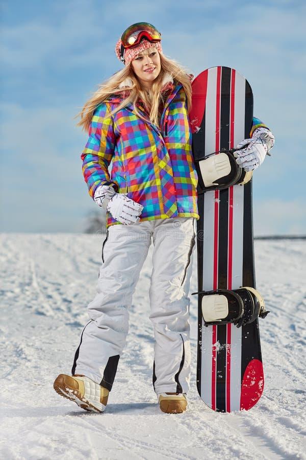 Νέα γυναίκα που κοιτάζει μακριά κρατώντας το σνόουμπορντ στο χιόνι στοκ φωτογραφίες
