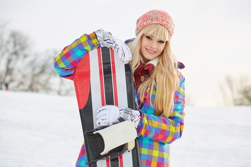 Νέα γυναίκα που κοιτάζει μακριά κρατώντας το σνόουμπορντ στο χιόνι στοκ φωτογραφία