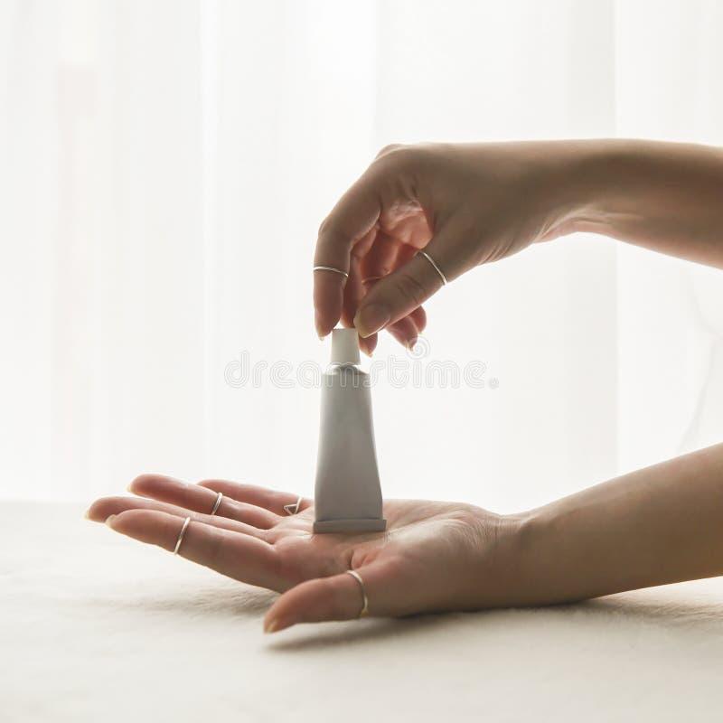 Νέα γυναίκα που κρατά έναν άσπρο σωλήνα της κρέμας για το δέρμα στοκ εικόνα