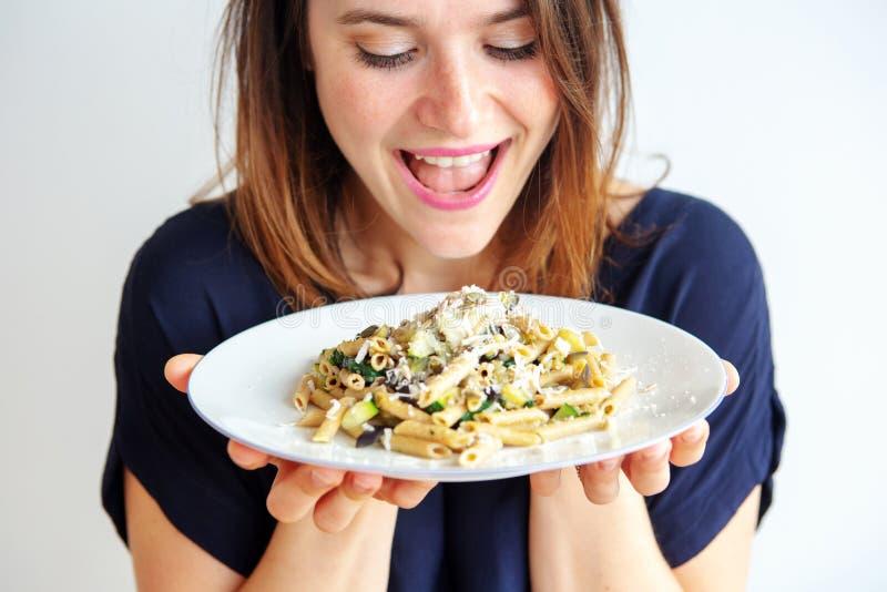 Νέα γυναίκα που κρατά ένα άσπρο πιάτο με τα ζυμαρικά και το τυρί στοκ φωτογραφία
