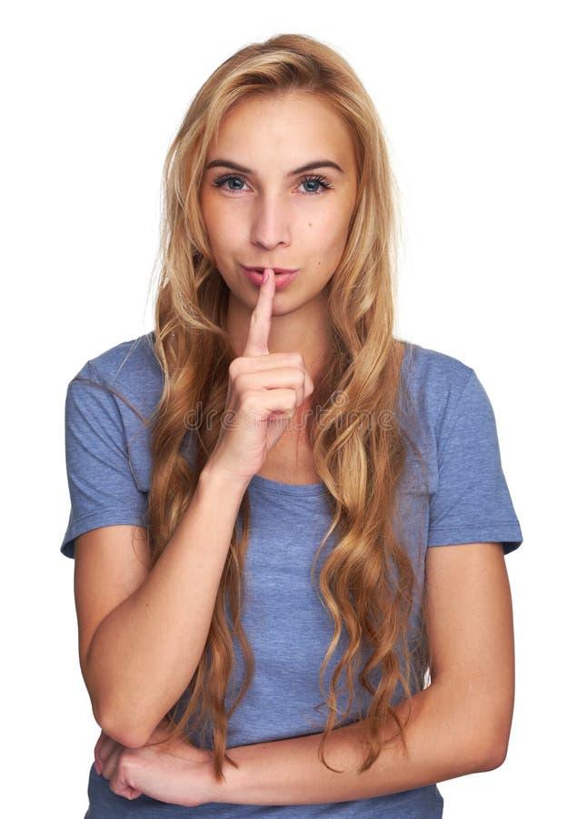 Νέα γυναίκα που κρατά ένα δάχτυλο στα χείλια της στοκ φωτογραφία με δικαίωμα ελεύθερης χρήσης