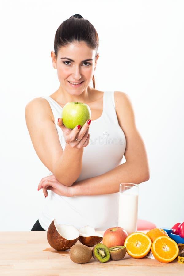 Νέα γυναίκα που κρατά ένα μήλο στο άσπρο υπόβαθρο στοκ εικόνα με δικαίωμα ελεύθερης χρήσης