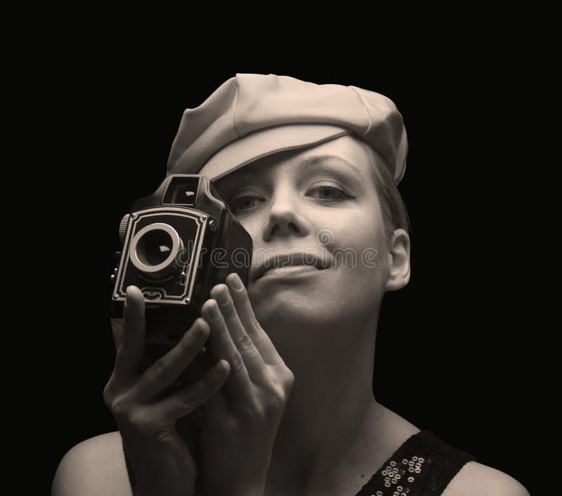 Νέα γυναίκα που κρατά μια αναδρομική κάμερα στοκ φωτογραφία