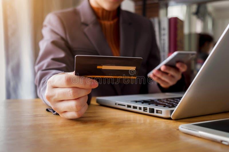 Νέα γυναίκα που κρατά μια πιστωτική κάρτα για να αγοράσει τις σε απευθείας σύνδεση αγορές στοκ εικόνα