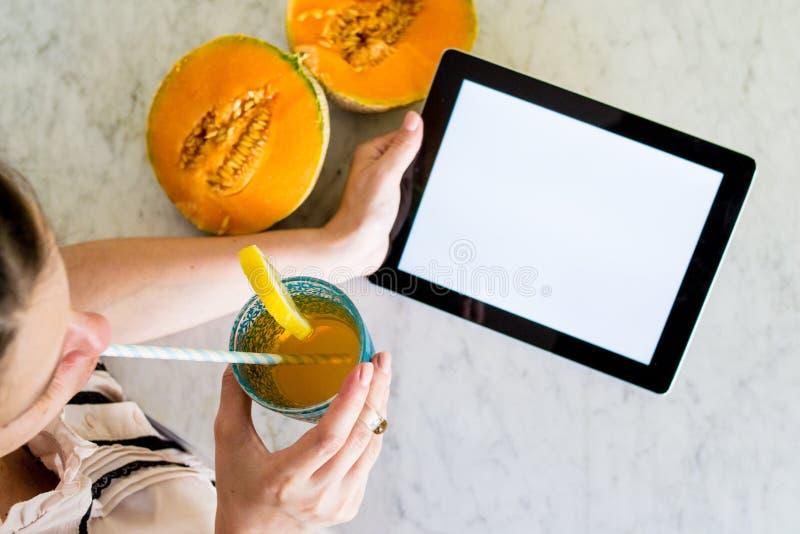 Νέα γυναίκα που κρατά μια ταμπλέτα με την οθόνη προτύπων με τα χέρια σε έναν πίνακα με τα θερινά φρούτα και το ποτό στοκ εικόνα με δικαίωμα ελεύθερης χρήσης
