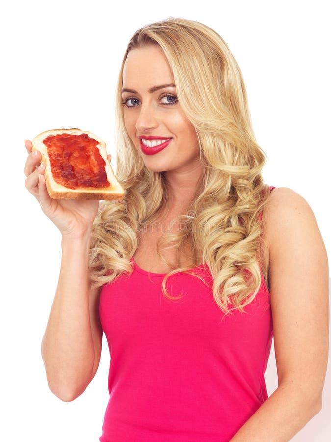 Νέα γυναίκα που κρατά μια φέτα της φρυγανιάς με τη μαρμελάδα που διαδίδεται στοκ φωτογραφία με δικαίωμα ελεύθερης χρήσης