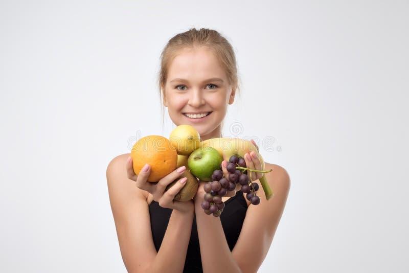 Νέα γυναίκα που κρατά τα διαφορετικά φρούτα στα χέρια στοκ εικόνα