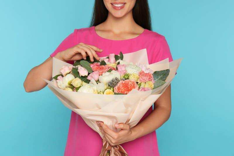 Νέα γυναίκα που κρατά την όμορφη ανθοδέσμη λουλουδιών στο ανοικτό μπλε υπόβαθρο, στοκ εικόνες