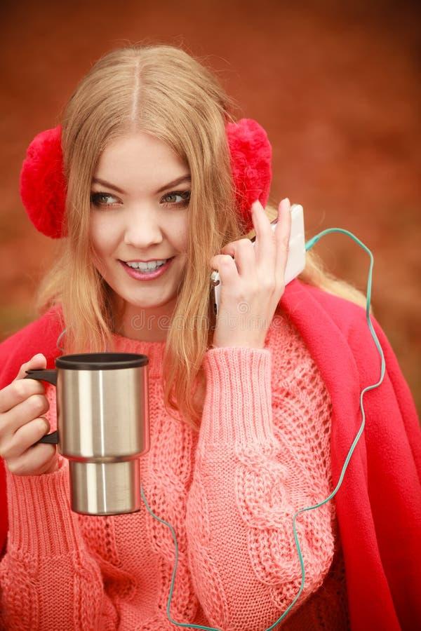 Νέα γυναίκα που κρατά τη θερμική κούπα στοκ φωτογραφία με δικαίωμα ελεύθερης χρήσης