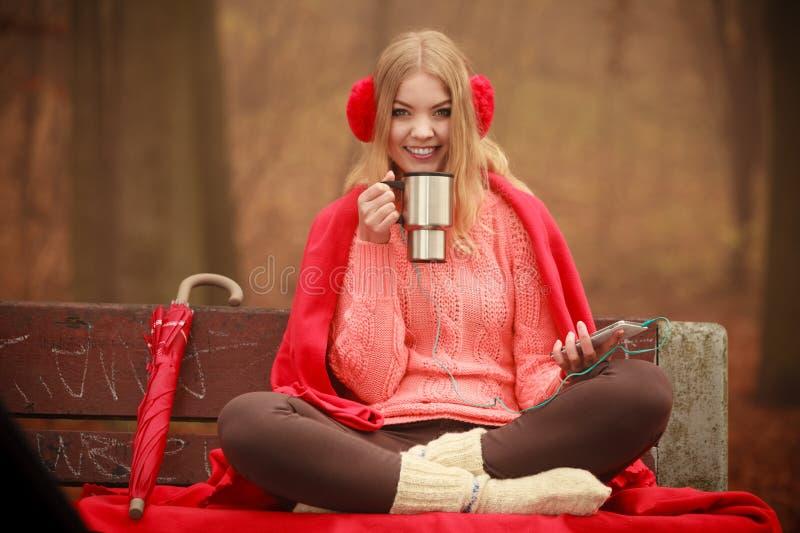 Νέα γυναίκα που κρατά τη θερμική κούπα στοκ φωτογραφία