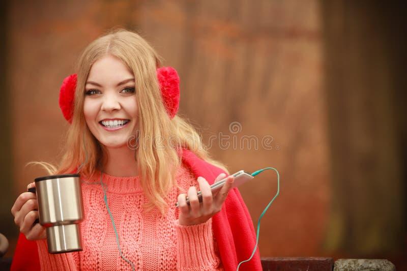 Νέα γυναίκα που κρατά τη θερμική κούπα στοκ εικόνα με δικαίωμα ελεύθερης χρήσης
