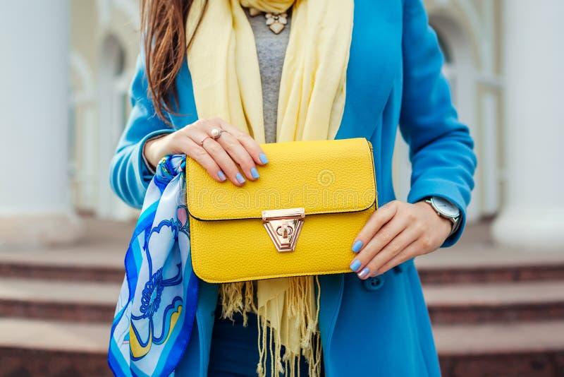 Νέα γυναίκα που κρατά τη μοντέρνη τσάντα και που φορά το καθιερώνον τη μόδα μπλε παλτό Θηλυκά ενδύματα και εξαρτήματα άνοιξη Μόδα στοκ εικόνα