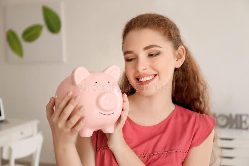 Νέα γυναίκα που κρατά τη piggy τράπεζα στο εσωτερικό Έννοια αποταμίευσης χρημάτων στοκ εικόνα