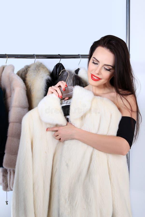 Νέα γυναίκα που κρατά το άσπρο παλτό γουνών βιζόν στοκ εικόνα