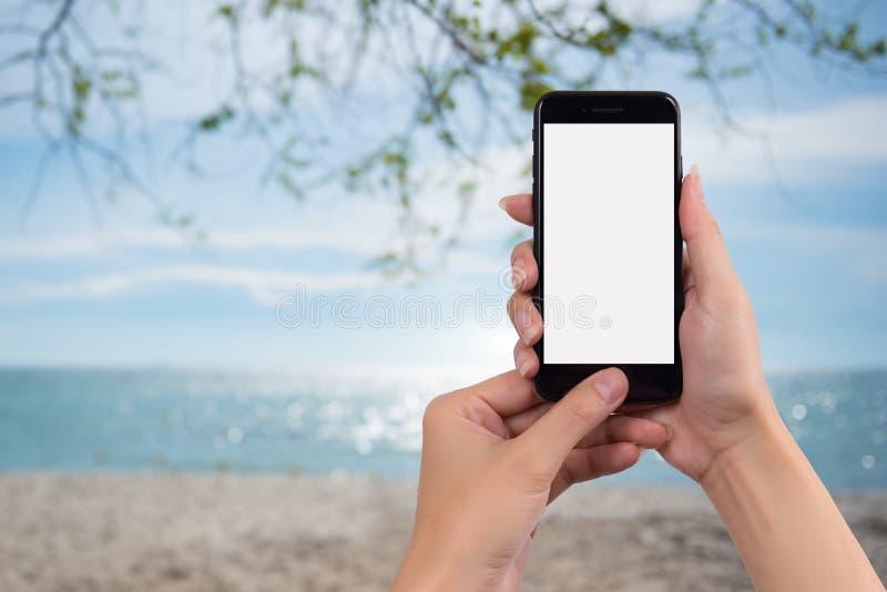 Νέα γυναίκα που κρατά το έξυπνο τηλέφωνο με το θολωμένο υπόβαθρο Για Gra στοκ εικόνες με δικαίωμα ελεύθερης χρήσης