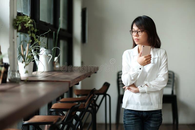Νέα γυναίκα που κρατά το κινητό τηλέφωνο και που υπερασπίζεται το παράθυρο HAV στοκ εικόνα με δικαίωμα ελεύθερης χρήσης