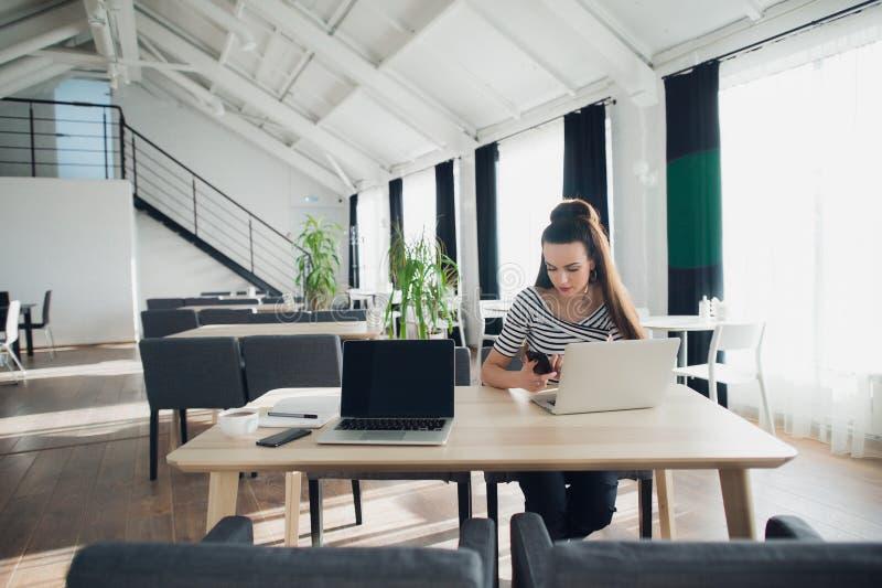 Νέα γυναίκα που κρατά το κινητό τηλέφωνο και τη δακτυλογράφηση SMS καθμένος στον ξύλινο πίνακα με τον ανοικτό φορητό προσωπικό υπ στοκ φωτογραφίες