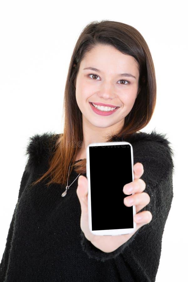 Νέα γυναίκα που κρατά το μαύρο κενό κενό έξυπνο τηλεφωνικό κινητό τηλέφωνο οθόνης στο χέρι της στοκ φωτογραφία