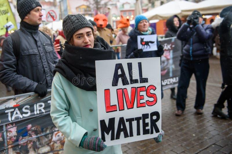 """Νέα γυναίκα που κρατά το σημάδι - όλες οι ζωές πειράζουν στα χέρια της, κατά τη διάρκεια """"του Μαρτίου για των ζώων στη Ρήγα, Λετο στοκ φωτογραφία"""