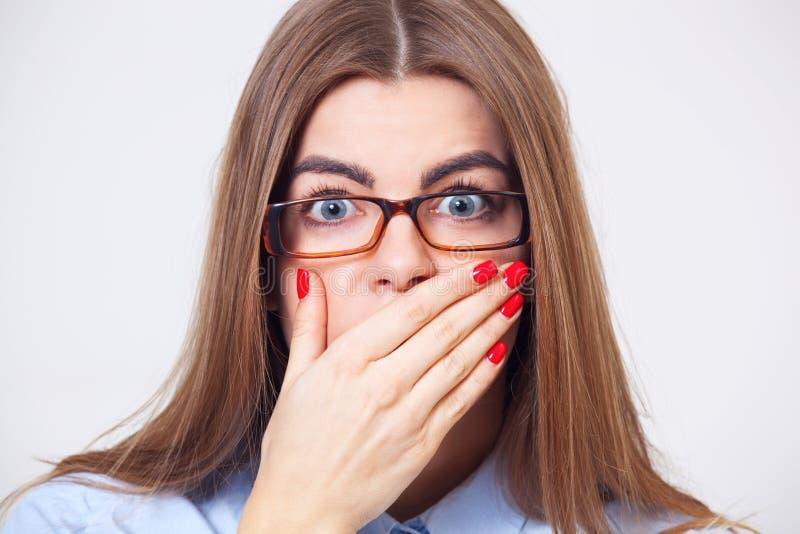 Νέα γυναίκα που κρατά το χέρι της κοντά στο στόμα που απομονώνεται στοκ φωτογραφία με δικαίωμα ελεύθερης χρήσης