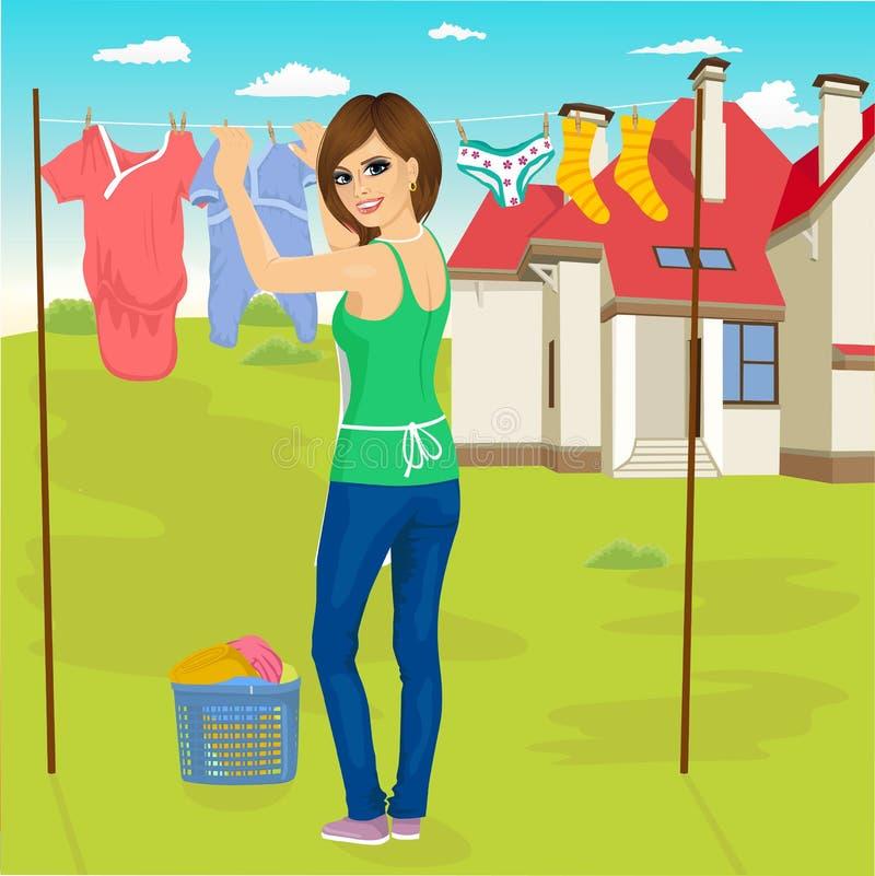 Νέα γυναίκα που κρεμά τα υγρά ενδύματα έξω που ξεραίνουν δίπλα στο οικογενειακό σπίτι ελεύθερη απεικόνιση δικαιώματος