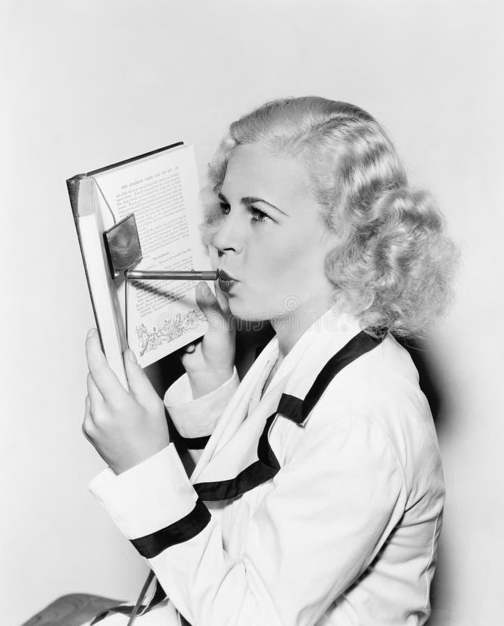 Νέα γυναίκα που κρύβει το πρόσωπό της πίσω από ένα βιβλίο που εφαρμόζει το κραγιόν (όλα τα πρόσωπα που απεικονίζονται δεν ζουν πε στοκ εικόνα