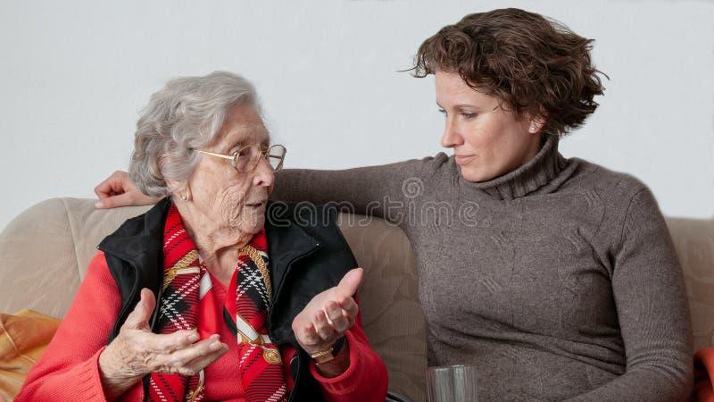 Νέα γυναίκα που μιλά με τη λυπημένη ανώτερη γυναίκα στοκ εικόνα