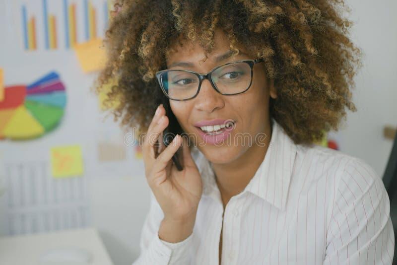 Νέα γυναίκα που μιλά στο smartphone στην αρχή στοκ φωτογραφία
