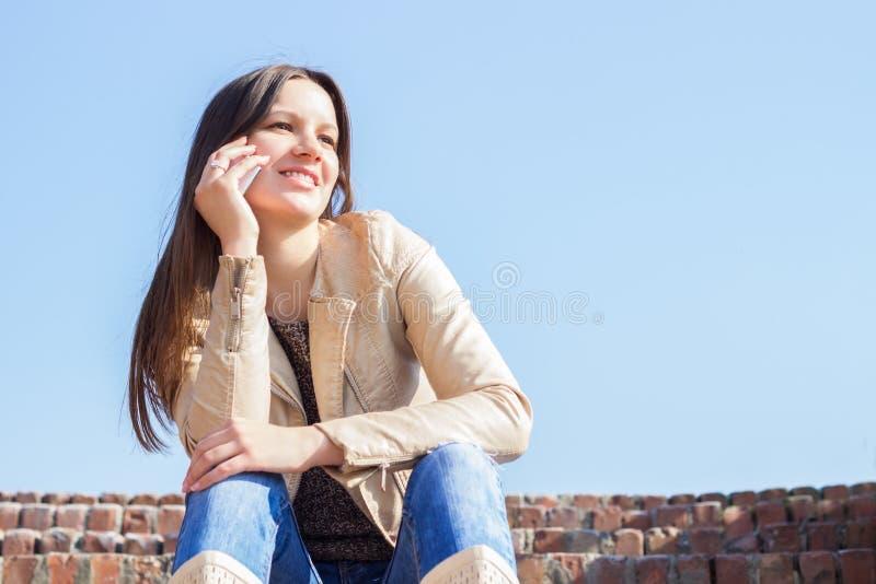 Νέα γυναίκα που μιλά στο κινητό τηλέφωνο στοκ φωτογραφία με δικαίωμα ελεύθερης χρήσης