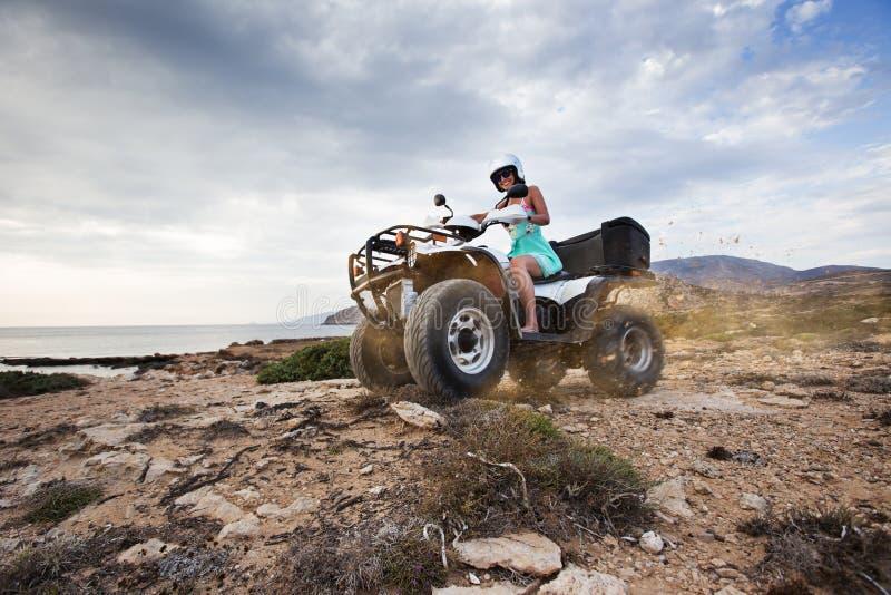 Νέα γυναίκα που οδηγεί το ποδήλατο τετραγώνων ATV στην παραλία Νησί Karpathos, Ελλάδα στοκ εικόνες