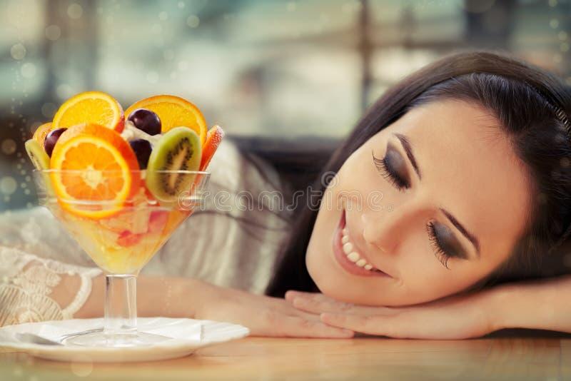 Νέα γυναίκα που ονειρεύεται με το επιδόρπιο σαλάτας φρούτων στοκ εικόνα