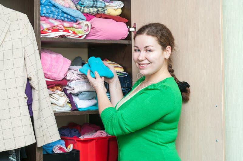Νέα γυναίκα που οργανώνει τα ενδύματα στην ντουλάπα στοκ φωτογραφία