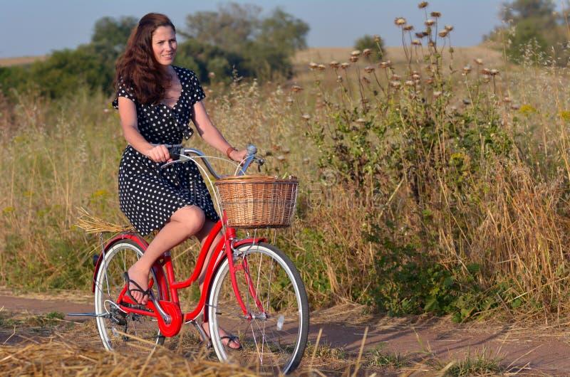 Νέα γυναίκα που οδηγά το εκλεκτής ποιότητας ποδήλατο στοκ φωτογραφία
