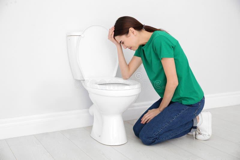 Νέα γυναίκα που πάσχει από τη ναυτία στο κύπελλο τουαλετών Διάστημα για το κείμενο στοκ εικόνες