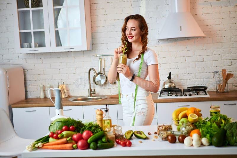 Νέα γυναίκα που πίνει τον πράσινο καταφερτζή στον πίνακα κουζινών με τα φρούτα και λαχανικά r Γεύμα Vegan και detox στοκ εικόνες