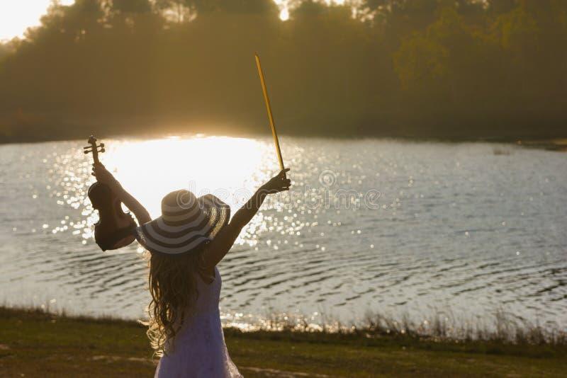 Νέα γυναίκα που παίζει το βιολί στο υπόβαθρο φύσης στοκ φωτογραφία με δικαίωμα ελεύθερης χρήσης