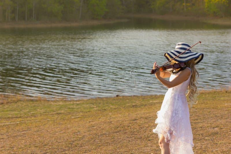 Νέα γυναίκα που παίζει το βιολί στο υπόβαθρο φύσης στοκ φωτογραφία