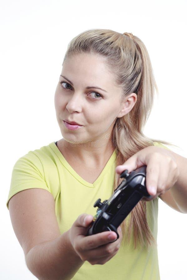 Νέα γυναίκα που παίζει το τηλεοπτικό παιχνίδι με το πηδάλιο στοκ φωτογραφία