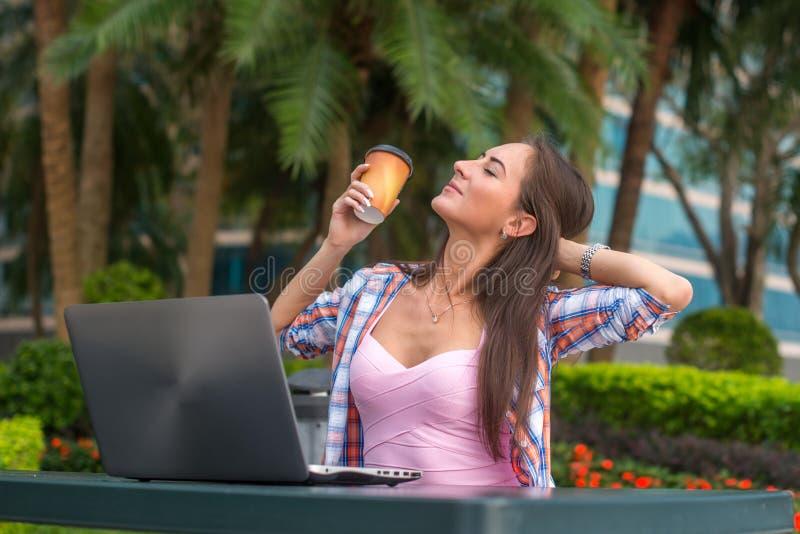 Νέα γυναίκα που παίρνει ένα σπάσιμο που χαλαρώνει από την εργασία για το lap-top στο πάρκο κρατώντας το φλιτζάνι του καφέ σε ένα  στοκ εικόνα με δικαίωμα ελεύθερης χρήσης