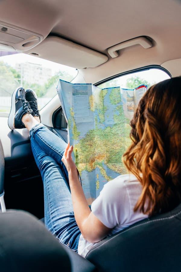 Νέα γυναίκα που παίρνει έτοιμη να ταξιδεψει με το αυτοκίνητο και που κοιτάζει στο χάρτη στοκ φωτογραφία