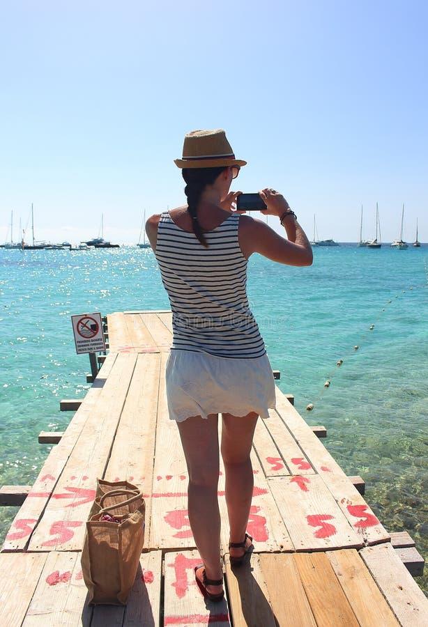 Νέα γυναίκα που παίρνει μια εικόνα από μια πλατφόρμα αποβαθρών σε διάφορες βάρκες που τοποθετούνται κοντά στην παραλία Ses Illete στοκ εικόνα