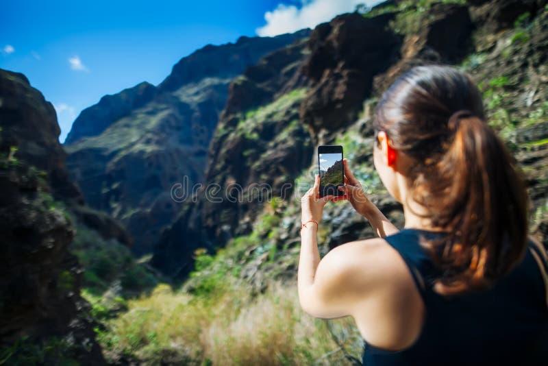 Νέα γυναίκα που παίρνει μια φωτογραφία με το τηλέφωνο καταπληκτικών βουνών της λ στοκ φωτογραφία